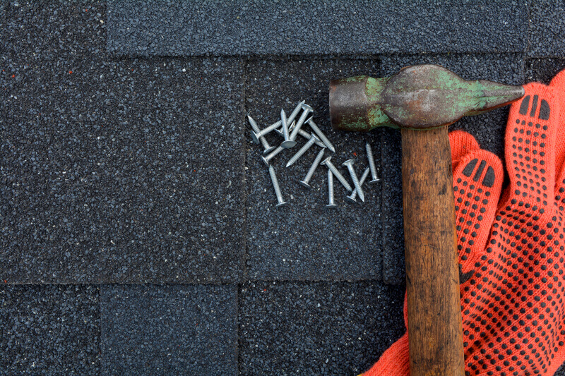 Hammer, nails and gloves on rooftop with shingles