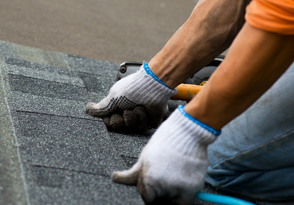 man with protective gloves laying roofing shingles - residential roofing in Aurora